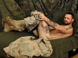 "gay porn Sergeant Miles || Sergeant Miles is the ultimate masculine hero. He spent his time in the U.S. Army Cavalry working on what he calls ""seventy tons of death"". Wearing his battle beard and desert camouflage uniform the soldier looks like he's armed to the teeth to fight or fuck. He loves the Army and the tank he worked on so much, he gets visibly excited when he talks about it. Injured in battle, Miles nearly lost his leg while saving one of his comrades' life. The only reason he's not still over there fighting is because his injury prevents him from being able to take on all the challenges the military requires. He hasn't let it hold him back from anything else, though. This stud is in top physical shape. You certainly can't tell that he was ever injured in battle. Settling back on the couch, he becomes more relaxed and starts working on his cock right away. He quickly begins to peel off his clothes revealing many tattoos, a bit of fur, and firm musculature. With a smirk on his face, he tugs at the pink stiffy protruding from his fly. Using both hands and some spit, he really goes to town on his meat while his steel blue eyes stare off in the distance. He springs to his knees and begins kneading his ass cheeks with one hand, while still jacking with the other. Gradually, his fingers work their way to his hole as he arches his back and thrusts his hips away from his cock. His hairy taint and pink balls are fully in view as his fingers plunge deep into depths of his sphincter. He finally works his hole over enough to bring himself to climax. Whacking at full speed, he grunts as his chest heaves. He squirts himself in the face as a giant load sprays out of his cock. He continues moaning as the remaining contents of his balls explode onto his chest."