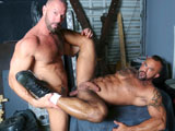 HighPerformanceMen.com is pleased to be the 1st to present Porn Legend Jon Galt and his life partner Vic Rocco in their initial return to porn performance. These two men are the epitome of what a High Performance Man is all about! Masculine, Confident and Sexy as Hell! The two embrace in a deep passionate kiss as their hands explore each others hard bodies. Soon their tank-tops are off revealing their ripped physiques as each explores the other with his tongue. They bury their tongues into each others ripe arm pits which intensifies their desire for each other. Soon their jeans are down around their knees and their cocks are struggling to break free from the confines of their jock-straps. Jon is the first on his knees as he does his best to take all of Vics enormously long and thick cock down his throat. Vic then returns the favor by deep throating every inch of Jons big cock. Vic then bends Jon over and drives his tongue deep into Jons eager hole. Jon begs for more as Vic begins to finger his hole deep and hard. He then spins Jon around and sucks his cock some more getting him all worked up before fucking him. The two then grind against each other as they spit on each others cocks and stroke each other. Vic then bends Jon over and drives his massive cock deep inside Jons muscular ass. At first the rhythm is slow and steady and then he drives his cock harder and deeper as Jon begs for more. Next Jon is laid out on his back as Vic pounds his hole long and deep. Unable to hold back any longer, Jon shoots a thick load all over his hairy stomach as Vic bends over and sucks out the last few drips of cum which is causing Jon to squirm in joy and laughter as he is very sensitive. Jon then drops to his knees as Vic shoots a thick creamy load all over Jons chest and then Jon sucks out the last remaining drops of Vics cum. Enjoy!