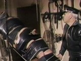 Vintage Scene From Roger Earl's Like Moths to a Flame (1988). a Slave (ted De Burin) Is Mummified on a Board With Electrician Tape by His Master (dirk Johnson). When the Taping Is Complete, the Slave Is Spun 360 Degrees on the Board and Begins Pissing All Over Himself!