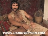 Bruno Bond films Aybars from the set of the Raging Stallion movie Tales of the Arabian Nights. Aybars lounges on Persian carpets in front of a crackling fire and strokes his big meat. He rubs his furry chest and shows off hairy hole while rubbing his thick cock until he blows his big load.