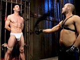 Muscle stud endures brutal suspension bondage in sharp twines.
