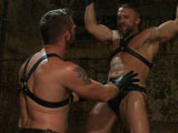 Morgan Black is cruising the dungeon, horny, and looking to play. He finds Dirk Caber working out and admiring his muscle alone near the creek. The two Doms make out, sniff each other's pits, and grope each other but Morgan has ideas to take control. He puts up Dirk's arms and flogs him while getting his cock sucked. He strips Dirk of his leather and beats his ass red while weights swing from his balls. Suspended 10 feet high in a crucifixion pose Morgan edges the Dom, clips clothes pins up and down his body and blasts him with the hose. He throws Dirk in a sling, cock still hard, and fucks the hell out of him making Dirk blow his load.